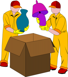 Two movers putting lamps inside a moving box.