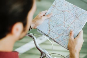 A man on a bike holding a map